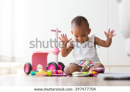 Portrait of little African American little girl sitting on the floor and playing  - Black people - stock photo