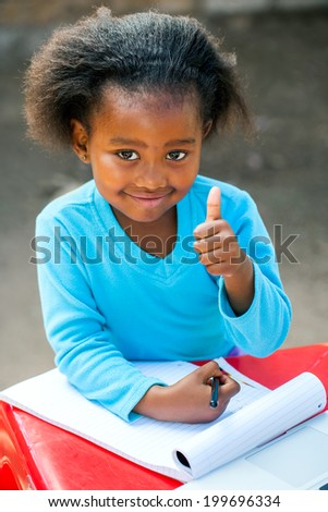 Portrait of little African girl doing thumbs up symbol at desk. - stock photo