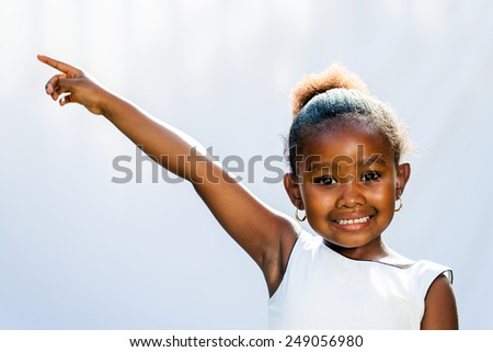 Portrait of little African girl pointing at corner with finger.Isolated against light background.