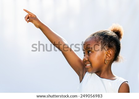 Portrait of little African girl pointing with finger and looking at corner.Isolated against light background.