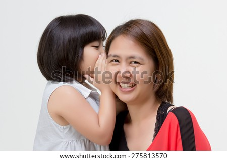Portrait of little Asian child whispering to her mother - stock photo