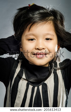 Portrait of Little asian cute Girl on gray background .