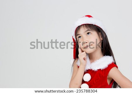Portrait of little Asian girl in red Santa hat thinking