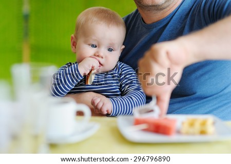 Portrait of little baby boy eating piece of bread - stock photo