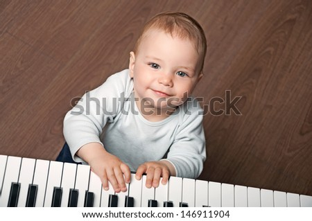 portrait of little baby child  play music on black and white piano keyboard