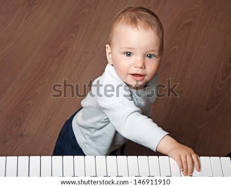 portrait of little baby child  play music on black and white piano keyboard - stock photo