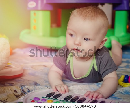 Portrait of little baby child playing music on black and white piano keyboard and looking aside. Small boy plays with the electronic piano. - stock photo