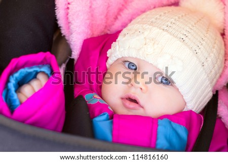 portrait of little baby girl in purple rose jacket and hat - stock photo