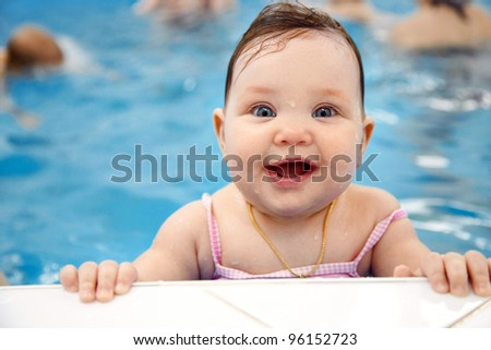 Portrait of little baby girl swimming  in swimming pool