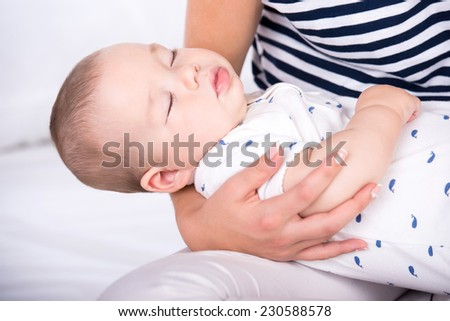 Portrait of little baby sleeping in mother's arms. - stock photo