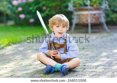 Portrait of little blond kid boy with toy sword, outdoors. On warm sunny summer day. - stock photo