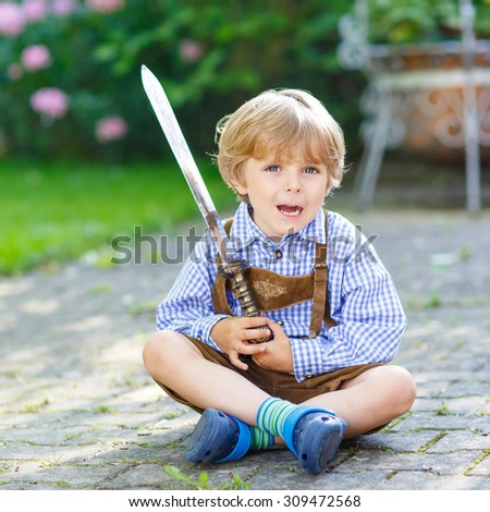Portrait of little blond kid boy with toy sword, outdoors. On warm sunny summer day. Family, happy childhood,  kids concept - stock photo