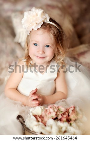 portrait of little blond smiling girl with flower on the head and wearing beautiful cream dress  - stock photo