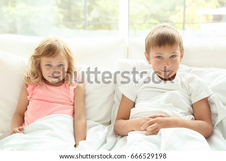 Portrait of little boy and girl in bed