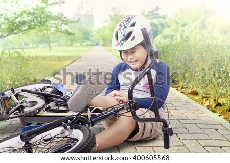 Portrait of little boy crying while holding his knee after falling from the bike at park - stock photo