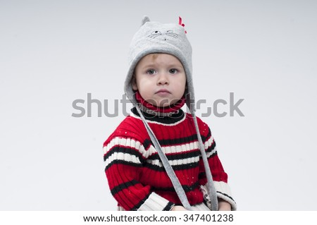 Portrait of little boy dressed in knitted pullover and hat. - stock photo
