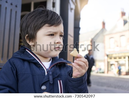 Portrait of little boy eating some cookies and looking out  while standing on walking street in the town, Kid food concept