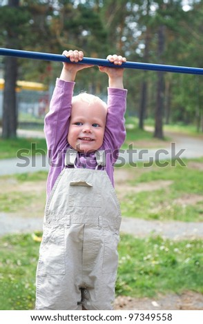 Portrait of little boy hang on horizontal bar in summer park - stock photo