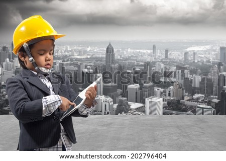 portrait of little boy holding a tablet device in both hands as he looks at the screen against balcony overlooking city dusky before rain falling with concept of real estate and engineering  - stock photo