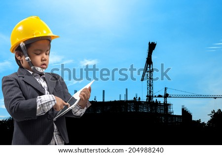 portrait of little boy holding a tablet device in both hands as he looks at the screen at construction site silhouetted on daytime blue sky in concept of real estate and engineering  - stock photo