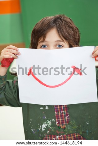 Portrait of little boy holding painting in front of face in kindergarten - stock photo