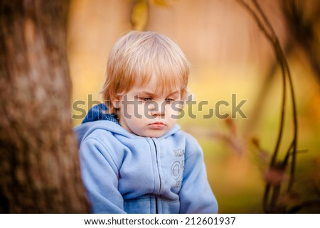 Portrait of little boy in autumn park with yellow foliage