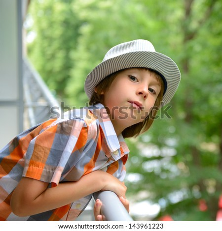Portrait of  little boy in hat looking out on balcony