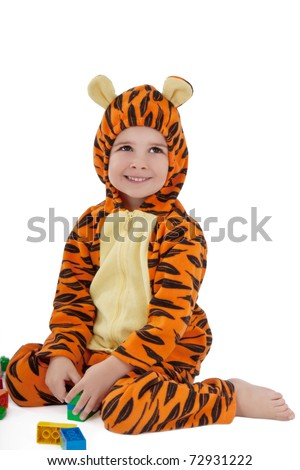 Portrait of little boy in tiger costume playing with construction set - stock photo