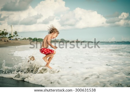 Portrait of little boy jumping on the beach at the day time - stock photo