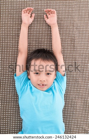 portrait of little boy laying on  - stock photo