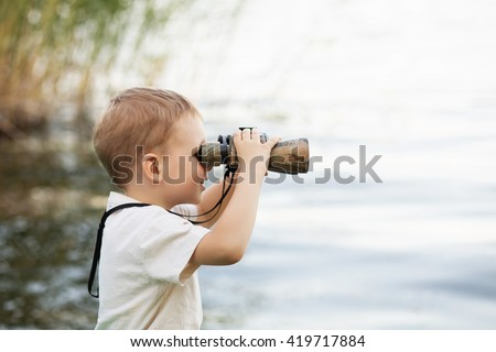 Portrait of little boy looking through binoculars on river bank. Cute kid with binoculars sitting on the pier on river - stock photo