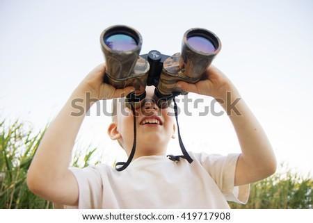 Portrait of little boy looking through binoculars on river bank. Cute kid with binoculars. The boy looks up at the sky through binoculars - stock photo