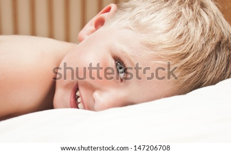Portrait of little boy lying in the bed. Just awakened happy boy. - stock photo