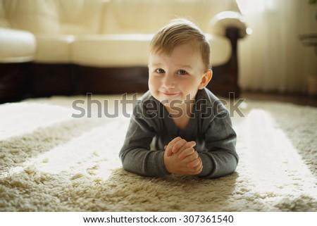 portrait of little boy lying on the carpet - stock photo