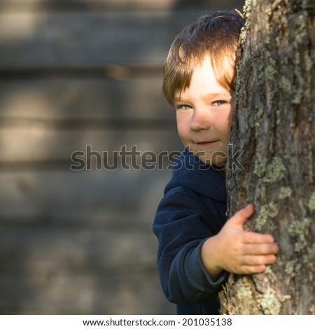 Portrait of little boy peeking from behind tree - stock photo
