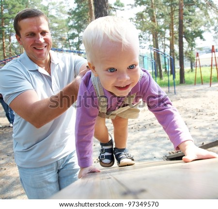 Portrait of little boy playing with father outdoor - stock photo