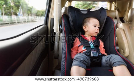 Portrait of little boy sitting in safety car seat