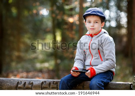 Portrait of little boy sitting on a bench outdoors - stock photo