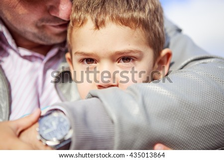 Portrait of little boy sitting on the bench next to his father - stock photo
