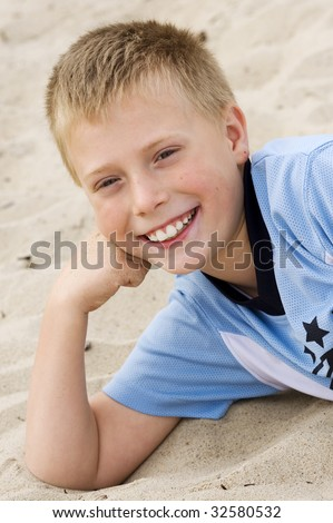 portrait of Little boy smiling laying down on the sand