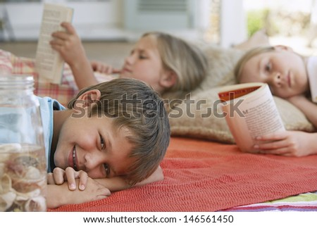 Portrait of little boy smiling while lying at porch with sisters reading books in background