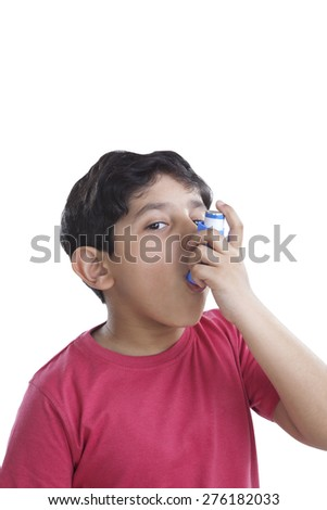 Portrait of little boy using an inhaler