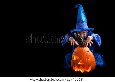 Portrait of little boy wearing halloween costume with pumpkin on dark background,Cute little boy trick or treating on Halloween. Isolated on black - stock photo