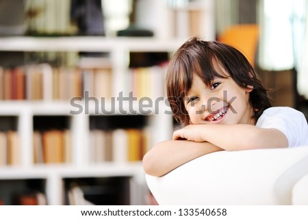 Portrait of little boy wearing white t-shirt, sitting at couch looking at camera smiling - stock photo