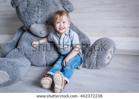Portrait of little boy with a big toy bear in the Studio posing emotions
