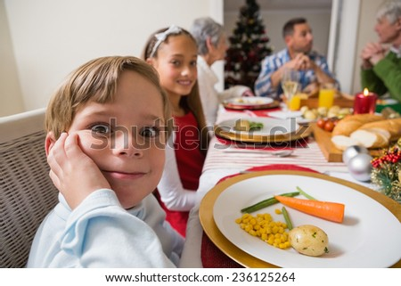 Portrait of little boy with a funny face at christmas dinner at home in the living room - stock photo