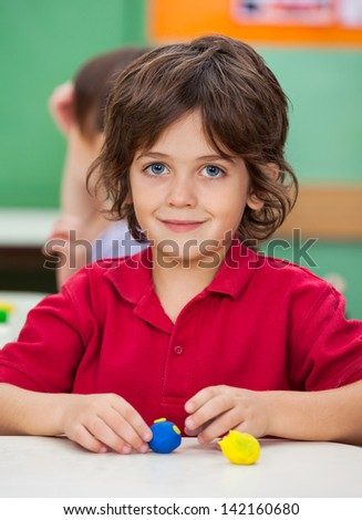 Portrait of little boy with clay at desk in classroom - stock photo