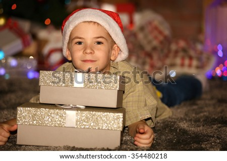 Portrait of little boy with gift boxes on a blurred background - stock photo