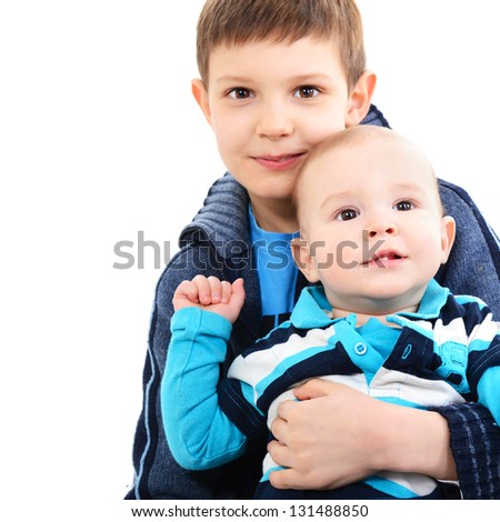 portrait of little boy with his baby brother, over white - stock photo