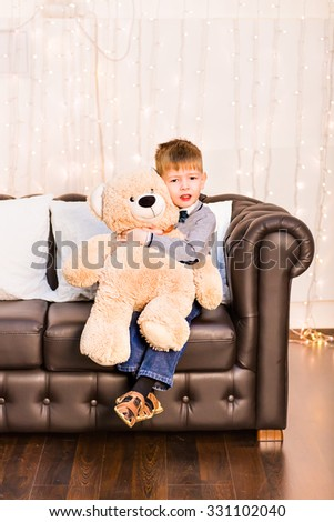 Portrait of little boy with teddy bear at home